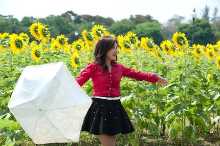 Pretty Asian woman in red dress hold umbrella is joyfully in sunflower field Stock Photo - 16901860