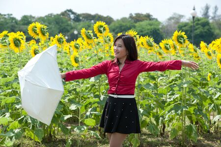 Pretty Asian woman in red dress hold umbrella is joyfully in sunflower field   photo