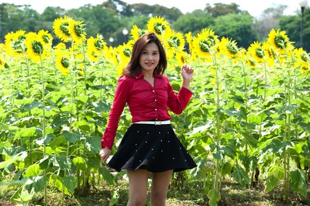 Pretty Asian woman in red dress is joyfully turned in sunflower field   photo
