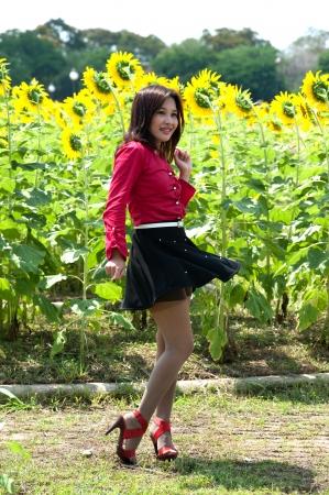 Pretty Asian woman in red dress is joyfully turned in sunflower field Stock Photo - 16901656