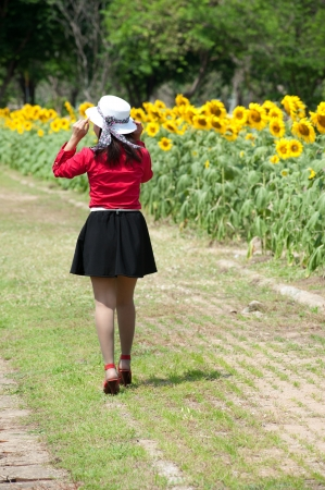 Pretty Asian woman in red dress walking in sunflower field  photo