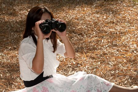 Pretty Asian woman sitting ground seeking binoculars   Stock Photo - 16901796