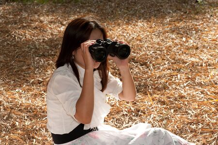 assis par terre: Jolie femme asiatique assis au sol jumelles qui cherchent