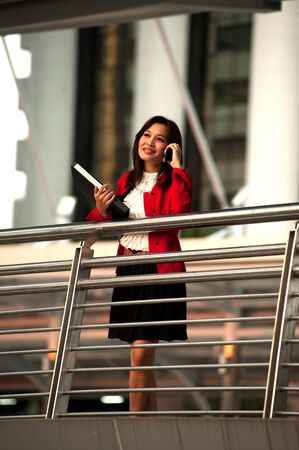 A pretty Asian business woman on the cell phone outside office building   photo