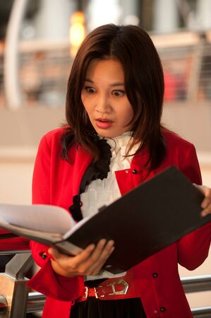 alarmed:  Pretty Asian businesswoman alarmed  Stock Photo