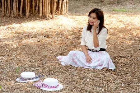 Pretty Asian woman in retro dress sitting in the park Stock Photo - 16968995