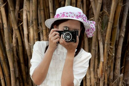 Pretty Asian woman use vintage camera in bamboos forest   photo