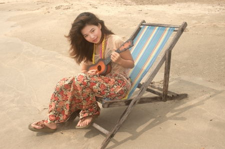 Pretty Asian woman playing ukulele on beach bed   photo