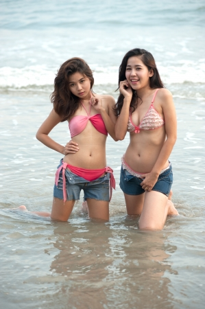 Twin pretty Asian woman posing on the beach   photo