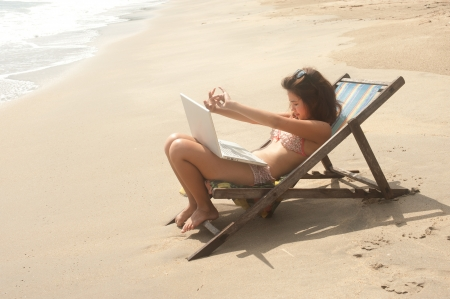 Pretty Asian woman working with laptop on beach bed   photo