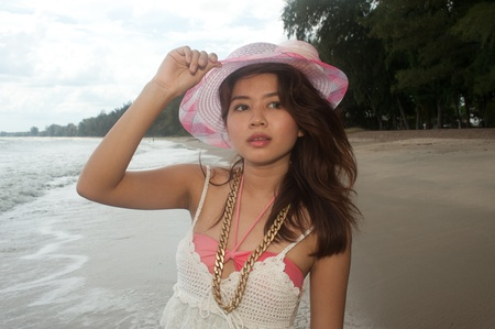 joyfully: Happy young pretty Asian woman posing and holding her hat at the beach