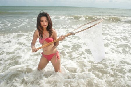 Pretty Asian woman with fishing scoop net   photo