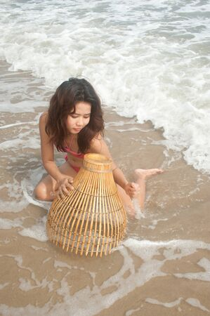 Pretty Asian woman with coop-like trap for catching fish in shallow water Stock Photo - 17230304