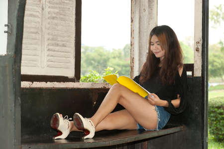 Asian woman reading in old train room   photo