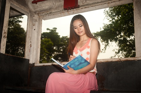 Beautiful young woman reading book in old train room of summer park   photo