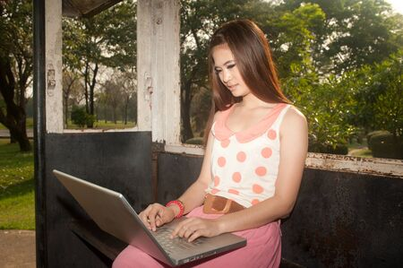 Asian woman working on laptops in the old train room   photo