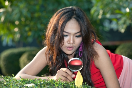 Pretty Asian woman with magnifying glass in the park Stock Photo - 17888475