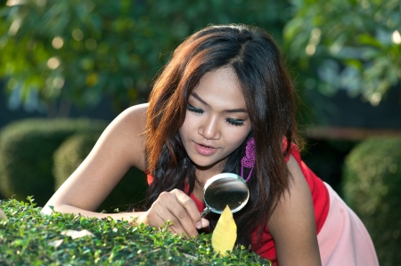 sagacious: Pretty Asian woman with magnifying glass in the park