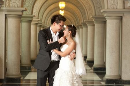 美しいアジアの花嫁とハンサムな新郎結婚式中にキリスト教の教会で の