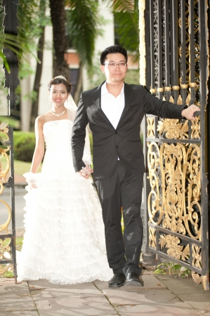 A beautiful Asian bride and handsome groom during wedding in the park   photo