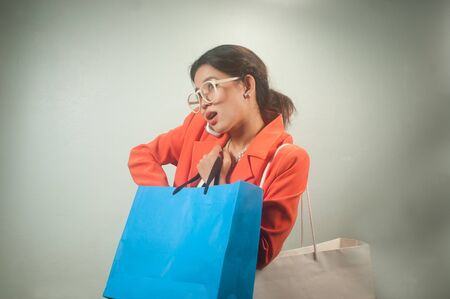Busy young Asian business woman with shopping bags on a  background   photo