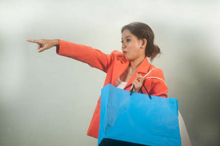 Young Asian business woman with shopping bags on a background   photo