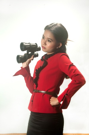 Pretty Asian business woman in red suit holding binoculars on background   photo