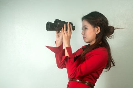 Pretty Asian business woman in red suit looking with binoculars on background   photo
