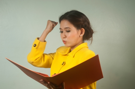 rote: Pretty young Asian businesswoman in yellow suit is complacent reading a file Stock Photo