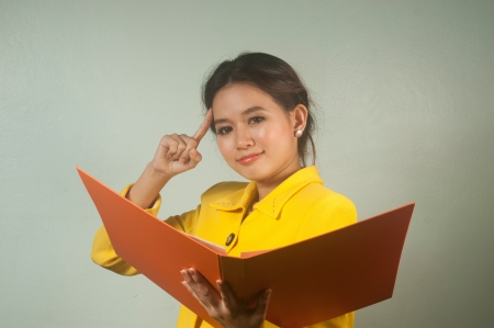 envision: Pretty young Asian businesswoman in yellow suit is ruminated and holding a file