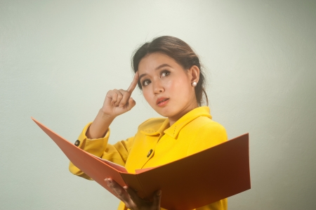 ruminate: Pretty young Asian businesswoman in yellow suit is ruminated and holding a file
