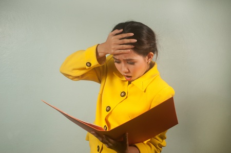 Pretty young Asian businesswoman in yellow suit is shocked and surprised   photo