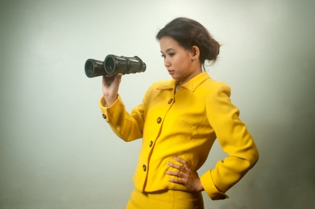 Pretty young Asian businesswoman in yellow suit holding a binoculars   photo