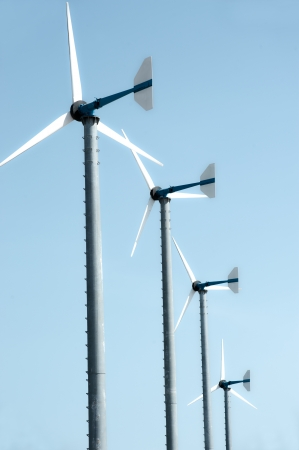 Wind turbines against blue sky produce electricity   photo