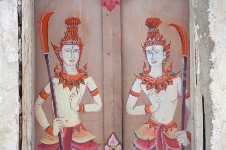 Ancient Thai art painting on the door of Buddhist Church made of teak wood 400 years at Wat Sri  Pho Chai temple in ,Loei Province,Northeast of Thailand  photo