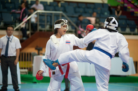 BANGKOK,THAILAND - SEPTEMBER 9   Female fighter attacks opponent with her foot in fight at Thailand Open Karate-Do Championship 2013 on Nimibutr National Indoor Stadium, September 9, 2013, Bangkok,Thailand