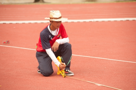 committee: Line committee measure the distance on Javelin Throw in Thailand Open Track and Field Championships 2013