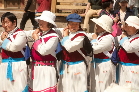 LIJIANG,CHINA-MARCH 17  A groups of Naxi nationality old women dressed in traditional clothing dancing Located in Dayan Old Town Squre street   Sifang Square   on March 17,2014 in Lijiang,Yunnan province,Southwestern of China  Redakční