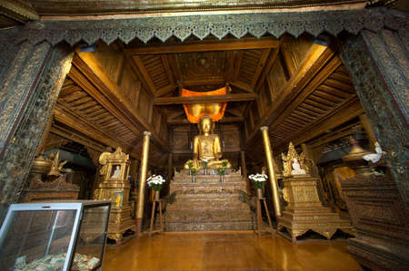 The golden sitting Buddha inside wooden Church of Nyan Shwe Kgua temple in Nuaungshwe,Myanmar. This Temple is a famous school of Buddhist Monk in Myanmar. Sajtókép