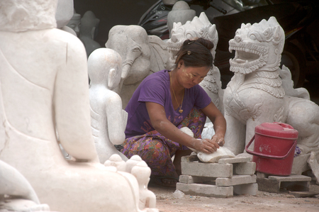 finishing touches: On the grounds women polishing on the finishing touches of a Buddha sculpture. Although the most expensive are carved from marble in Mandalay,Myanmar.