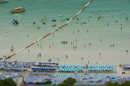 sunbeds: Hat Ta Waen Beach in Koh Larn Island with tourists, sunbeds and umbrellas on the hot summer day.