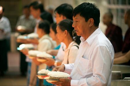 limosna: Pueblos de espera dan limosnas a un monje budista.