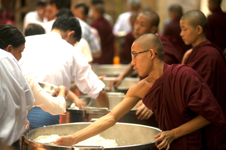 alms: Peoples giving with alms to a Buddhist Monk in Myanmar. Editorial