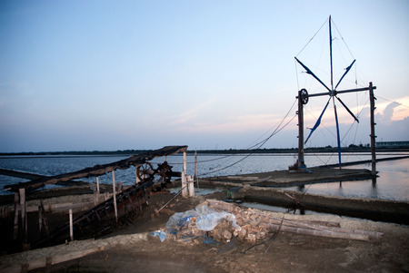Ancient Thai traditional water wheel pump and wind mill use for move the sea water into the salt field in Thailand. photo