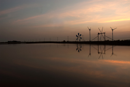 Sunset at ancient and new wind mill use for move the sea water into the salt field in Thailand. photo