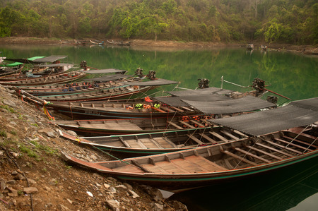 waiting passengers: Row of traditional tourist boat waiting passengers on Cheow Larn lake in Khao Sok National park, Thailand. Editorial