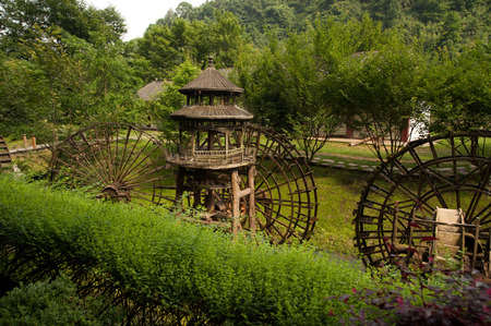 waterwheel: Wooden waterwheel front of Huanglong cave or Yellow Dragon cave in China. Stock Photo