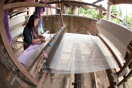 minority: Lua or Thin Hill Tribe Minority weaving with loom in Thailand. Editorial