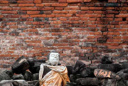 dilapidated: Head of dilapidated Buddha on the wall in temple.