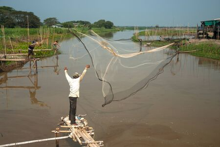 Hurl: Traditional Thai fisherman casting in river. Stock Photo
